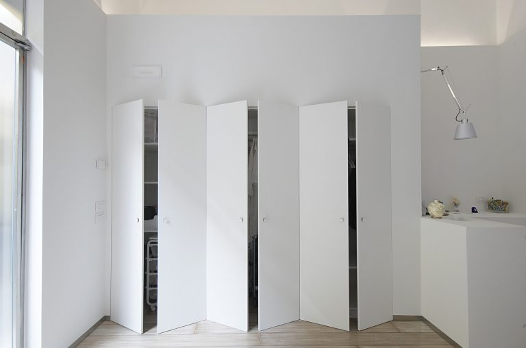 foto di armadio filomuro con ante alte aperte